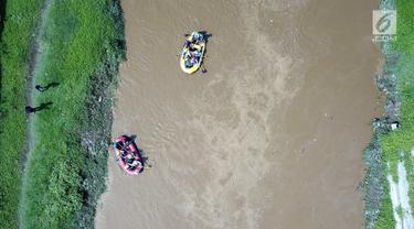 Peserta dengan perahu karet  menyusuri Sungai Ciliwung sambil membersihkan sampah pada acara Bersih-Bersih Sungai Ciliwung, Jakarta, Minggu (08/4). Kegiatan tersebut merupakan rangkaian HUT Kementerian BUMN. (Liputan6.com/Fery Pradolo)