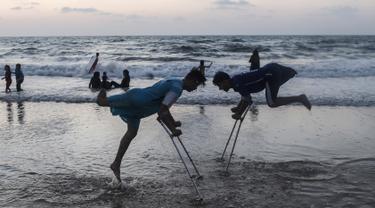 Dua pemuda Palestina Mohammed Eliwa (kiri) dan Ahmed al-Khoudari melakukan pemanasan sebelum bermain sepak bola di pantai di Kota Gaza (20/9/2019). Eliwa 17 tahun dan Ahmed al-Khoudari 20 tahun kehilangan satu kakinya saat bentrok di perbatasan Israel. (AFP Photo/Mahmud Hams)