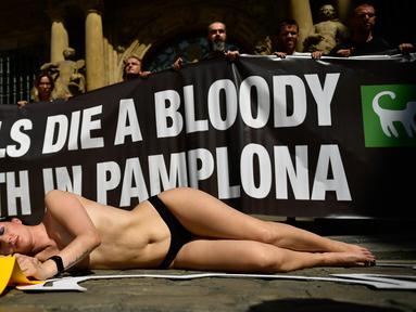 Aktivis yang bertelanjang dada berbaring di jalan saat menggelar protes terhadap adu banteng di Pamplona, Spanyol, Jumat (5/7/2019). Aksi protes ini digelar sehari sebelum pembukaan Festival San Fermin. (AP Photo/Alvaro Barrientos)