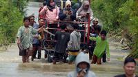 Warga melintasi banjir di Desa Sindangsari, Kabupaten Bekasi, Jawa Barat, Rabu (24/2/2021). Tim Tanggap Bencana Land Rover Club Indonesia (LRCI) melakukan drop logistik dan mengevakuasi warga yang sakit di Desa Sindangsari. (merdeka.com/Imam Buhori)