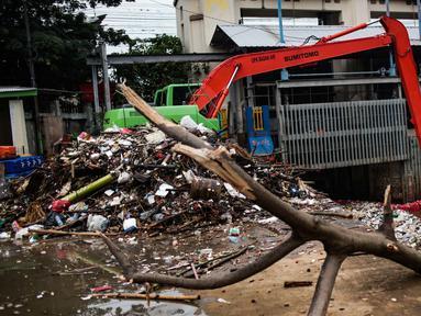 Alat berat beroperasi mengangkut sampah yang menumpuk di Pintu Air Manggarai, Jakarta, Selasa (4/12). Tingginya intensitas hujan di wilayah Jabodetabek membuat sampah yang terbawa arus sungai menumpuk di Pintu Air Manggarai. (Liputan6.com/Faizal Fanani)