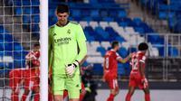 Kiper Real Madrid Thibaut Courtois tertunduk lesu usai Ivan Rakitic cetak gol (AFP)