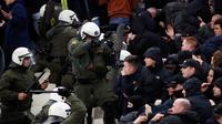 Polisi anti huru-hara Yunani bentrok dengan suporter Ajax Amsterdam sebelum pertandingan Liga Champions melawan AEK Athena di Stadion Olimpiade Athena, Selasa (27/11). Akibat bentrokan ini, sejumlah pendukung Ajax terluka. (AP/Thanassis Stavrakis)