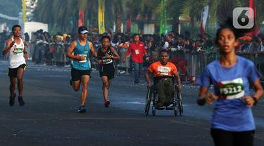 Peserta disabilitas memacu kursi roda balapnya di antara para peserta lomba lari bertajuk Lo Gue Run (LGR) 2020 di Kompleks Monas, Jakarta Pusat, Minggu (26/1/2020). Kodam Jayakarta menggelar lomba lari 'Loe Gue Run' yang merupakan puncak perayaan HUT ke-70 Kodam Jaya. (Liputan6.com/Johan Tallo)