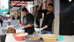 Seorang pekerja Palestina membagikan makanan gratis pada hari keempat Ramadan di Deir al-Balah, Jalur Gaza tengah, pada 27 April 2020. Warga Palestina merayakan Ramadan, bulan suci umat Islam, di tengah situasi ekonomi yang memburuk akibat pandemi COVID-19. (Xinhua/Rizek Abdeljawad)