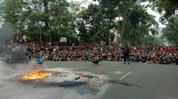 Massa aksi yang dipukul mundur ke Jalan Diponegoro arah Gedung Sate tetap bertahan. Aksi bakar ban di depan Gedung Sate Bandung sambil berorasi. (Liputan6.com/Huyogo Simbolon)