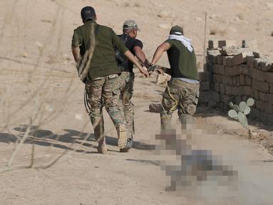 Para tentara Irak menyeret jenazah militan ISIS  dengan tali sebelum dimakamkan di dekat Karmah, selatan Mosul, Irak (11/11). Jenazah kelompok ISIS ditemukan tewas setelah terlibat kontak senjata dengan pasukan koalisi Irak. (REUTERS/Goran Tomasevic)