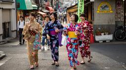 Sejumlah wanita memakai pakaian tradisional berjalan di sepanjang jalan perbelanjaan Yanaka Ginza di pusat Tokyo (30/9/2019). Bagian kota yang sudah tua ini terhindar dari pengeboman Sekutu selama Perang Dunia II dan selamat dari Gempa Besar Kanto dan Kebakaran tahun 1923. (AFP Photo/Odd Andersen)