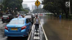 Suasana kawasan Gambir yang direndam banjir di Jakarta, Kamis (15/2). Banjir tersebut mengakibatkan jalan di sekitar lokasi terpaksa ditutup karena tidak bisa dilalui kendaraan bermotor. (Liputan6.com/Immanuel Antonius)
