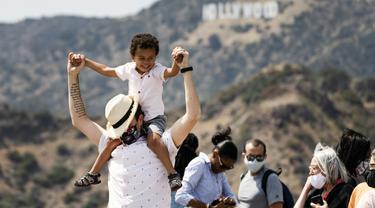 Pengunjung mengenakan masker di luar ruangan saat mengambil gambar tanda Hollywood di Observatorium Griffith di Los Angeles, Senin (17/5/2021). California mempertahankan aturan mengenakan masker hingga negara bagian itu mencabut pembatasan COVID-19 pada 15 Juni. (AP Photo/Damian Dovarganes)