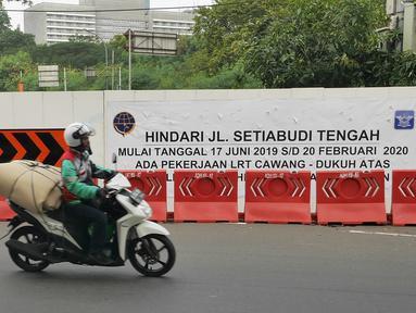 Pengendara sepeda motor melintas dekat proyek pembangunan jalur kereta Light Rail Transit (LRT) di Jalan Setiabudi Tengah, Jakarta, Senin (17/6/2019). Jalan Setiabudi Tengah ditutup mulai 17 Juni 2019 hingga 20 Februari 2020. (Liputan6.com/Herman Zakharia)