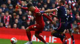 Gelandang Liverpool, Roberto Firmino, berebut bola dengan pemain Bournemouth pada laga lanjutan Premier League 2019-2020 di Anfield, Liverpool, Sabtu (7/3) malam WIB. Liverpool menang 2-1 atas Bournemouth. (AFP/Geoff Caddick)