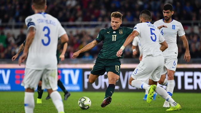 Striker timnas Italia, Ciro Immobile berebut bola dengan pemain Yunani, Dimitris Siovas dan Andreas Bouchalakis pada pertandingan grup J babak kualifikasi Piala Eropa 2020 di Stadio Olimpico, Sabtu (12/10/2019). Italia lolos ke putaran final setelah mengalahkan Yunani, 2-0. (Alberto PIZZOLI / AFP)