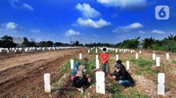 Warga melakukan ziarah makam menyambut bulan Ramadhan 1442 H di Tempat Pemakaman Umum (TPU) khusus covid-19 di Srengseng sawah 2, Jakarta Selatan, Jumat (09/04/2021). Tradisi ziarah makam dalam menyambut bulan Ramadhan setiap tahun dilakukan oleh umat Islam. (merdeka.com/Arie Basuki)