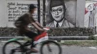 Pesepeda melintasi mural bergambar sosok Bung Hatta di Jalan Pluit Raya III, Jakarta, Minggu (10/8/2020). Mural itu diharapkan menjadi media agar masyarakat selalu mengingat sejarah dan menghargai jasa para pahlawan dalam memerdekakan Tanah Air. (merdeka.com/Iqbal Nugroho)