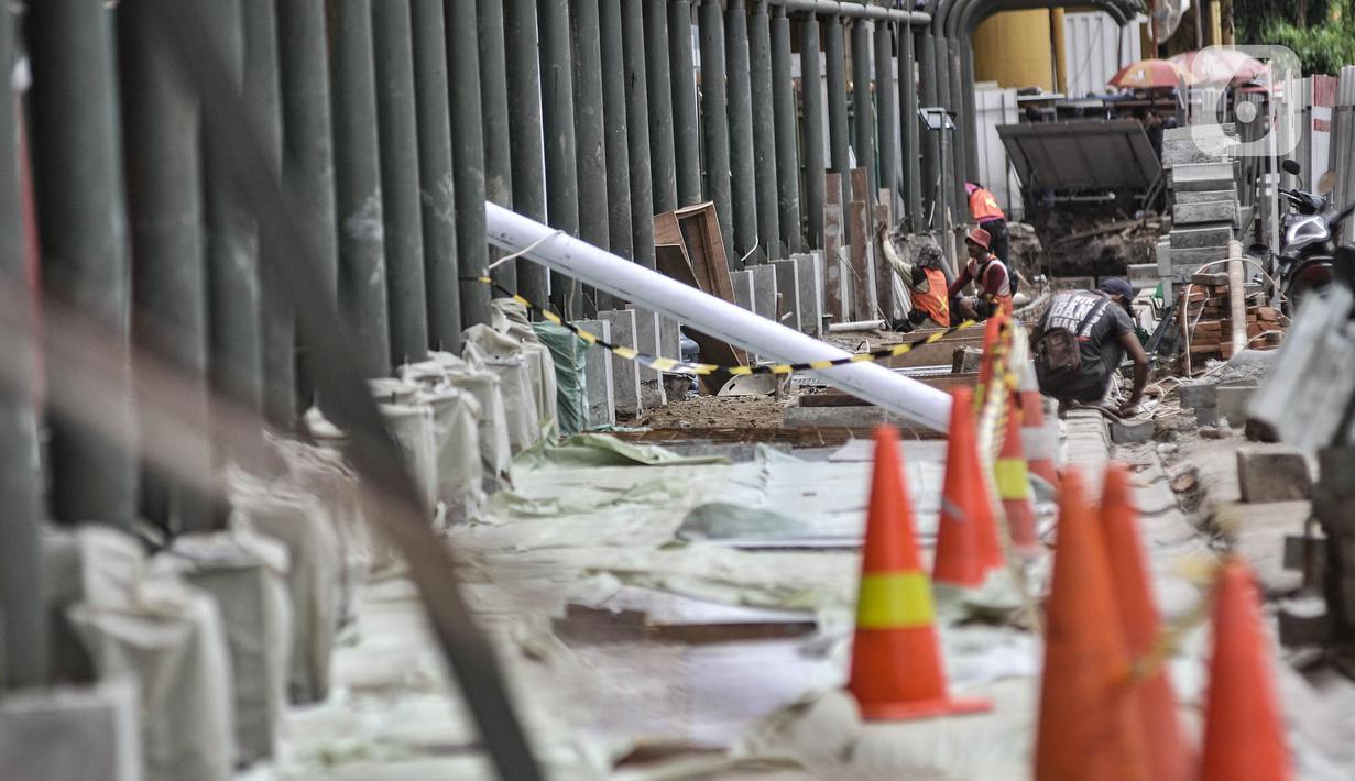 Pekerja saat menyelesaikan pembangunan jalur pedestrian atau pejalan kaki di Stasiun Gondangdia, Jakarta Pusat, Kamis (8/4/2021). Stasiun Gondangdia akan menjadi salah satu stasiun terpadu yang pembangunannya meliputi penataan pedestrian, tempat khusus bagi pedagang. (merdeka.com/Iqbal S. Nugroho)