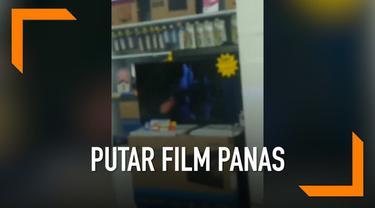 Sebuah tv yang sedang dipajang pada sebuah pusat perbelanjaan terekam kamera memutarkan film panas.