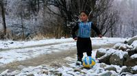 Murtaza Ahmadi, anak laki-laki Afghanistan, bermain bola sambil mengenakan kaos kantong kresek timnas Argentina milik Lionel Messi di  kabupaten Jaghori, provinsi Ghazni, 29 Januari 2016. Sebelumnya, foto Murtaza itu menyebar luas di dunia maya (STR/AFP)