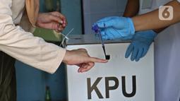 Petugas menandai jari warga dengan tinta usai mencoblos saat Pilkada Depok di TPS 56, Mekarjaya, Depok, Rabu (9/12/2020). TPS 56 menggunakan tema kesehatan untuk menarik warga menggunakan hak pilih dan mengingatkan protokol kesehatan di masa Pandemi COVID-19.  (Liputan6.com/Herman Zakharia)