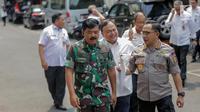 Panglima TNI Marsekal Hadi Tjahjanto (kiri) berbincang dengan Kapolri Tito Karnavian (kanan) saat akan memberi keterangan usai rapat koordinasi tertutup di Kantor Kemenko Polhukam, Jakarta, Selasa (24/9/2019). Ada tiga isu nasional yang dibahas dalam rapat tersebut. (Liputan6.com/Faizal Fanani)