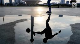 Seorang warga bermain sepak bola di kawasan Monas, Jakarta, Rabu (13/2). Kawasan Monas menjadi tempat favorit warga Ibu Kota untuk berolahraga. (Bola.com/M Iqbal Ichsan)