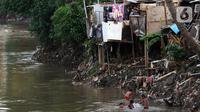 Anak-anak bermain di bantaran sungai Ciliwung, Pemukimannya, Manggarai, Jakarta, Selasa (29/9/2020). Irjen Kemenkeu Sumiyati mengatakan Pengangguran dan juga angka kemiskinan diperkirakan akan naik cukup signifikan. (Liputan6.com/Johan Tallo)