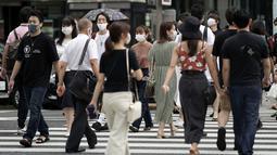 Orang-orang yang memakai masker wajah untuk membantu mencegah penyebaran virus corona melintasi jalan perbelanjaan di Tokyo, Kamis (10/9/2020). Ibu kota Jepang itu mengonfirmasi lebih dari 270 kasus virus corona pada Kamis. (AP Photo / Eugene Hoshiko)