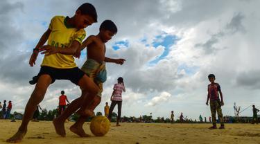 Anak-anak Rohingya bermain sepak bola di kamp pengungsi Kutupalong di Ukhia, Bangladesh, 19 Juli 2018. Piala Dunia 2018 mungkin sudah berakhir, namun demam pesta akbar sepak bola itu masih terasa di kamp pengungsi terbesar di dunia. (AFP/Munir UZ ZAMAN)