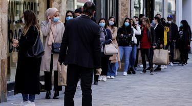 Pelanggan mengantre di pintu masuk sebuah toko pakaian pada hari pertama pelonggaran lockdown secara bertahap di Brussel, Senin (11/5/2020). Warga Belgia rela mengantre selama beberapa jam sebelum toko dibuka untuk berbelanja pertama kalinya sejak lockdown pada Maret lalu. (Kenzo TRIBOUILLARD/AFP)