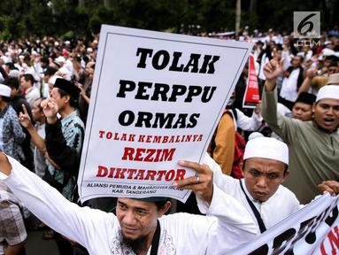 Peserta aksi membawa poster saat berunjuk rasa di Pintu Barat Monas, Jakarta, Selasa (18/7). Dalam aksinya mereka menilai Perppu Ormas menimbulkan tindakan diktator (kesewenang-wenangan). (Liputan6.com/Faizal Fanani)