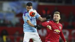 Bek Manchester United, Luke Shaw, duel udara dengan gelandang Manchester City, Riyad Mahrez, pada laga Premier League di Stadion Old Trafford, Minggu (8/3/2020). Manchester United menang dengan skor 2-0. (AP/Dave Thompson)