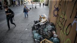 Orang-orang berjalan melewati tumpukan sampah yang diakibatkan pemogokan petugas sampah di Santiago (14/11/2019). Protes kekerasan meletus di ibukota Chile, Santiago, pada Selasa ketika mata uang negara itu turun ke level terendah dalam sejarah. (AFP/Javier Torres)
