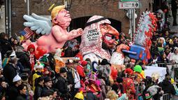 Karakter yang menggambarkan Presiden AS Donald Trump sebagai malaikat berada di belakang Putra Mahkota Arab Saudi Mohammed bin Salman dengan gergaji berdarah memeriahkan Karnaval Rose Monday di Duesseldorf, Jerman, Senin (4/3). (AP Photo/MartinMeissner)
