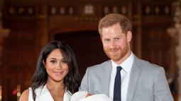 Pangeran Harry dan Meghan Markle berpose  dengan bayi laki-lakinya yang baru lahir di St George's Hall di Windsor Castle di Windsor, London (8/5/2019). Pangeran Harry dan Meghan Markle melahirkan anak pertama mereka di Frogmore Cottage pada Senin pagi, 6 Mei 2019.  (AFP Photo/Dominic Lipinski)