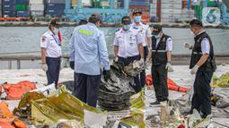 Petugas KNKT memeriksa bagian turbin pesawat Sriwijaya Air dihari kelima yang jatuh di perairan Pulau Seribu, di Dermaga JICT, Jakarta,  Rabu (13/1/2021). Pengangkatan mesin turbin pesawat Sriwijaya Air SJ 182 itu menggunakan crane milik KRI Cucut 866. (Liputan6.com/Faizal Fanani)