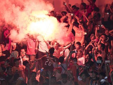 Suporter Persija Jakarta, The Jakmania, menyalakan flare usai mengalahkan Mitra Kukar pada laga Liga 1 di SUGBK, Jakarta, Minggu (9/12). Persija menang 2-1 atas Mitra. (Bola.com/Yoppy Renato)