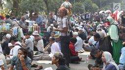Pedagang asongan menawarkan dagangannya di sela-sela massa aksi di sekitaran Jalan Medan Merdeka Barat, Jakarta, Kamis (27/6/2019). Massa yang melakukan aksi terkait sidang putusan perselisihan hasil Pilpres 2019 memberi keuntungan bagi para pedagang. (Liputan6.com/Helmi Fithriansyah)