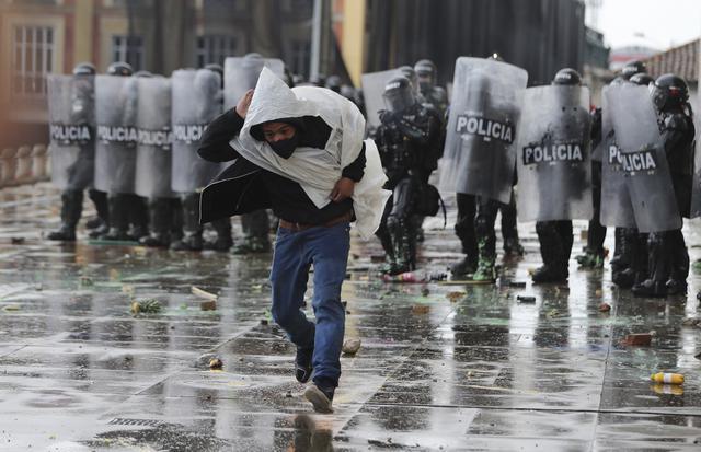 Seorang pria melarikan diri dari polisi setelah melemparkan batu ke arah mereka selama pemogokan nasional untuk memprotes reformasi pajak yang diusulkan pemerintah, di Bogota, Kolombia, Rabu (28/4/2021). (AP Photo/Fernando Vergara)