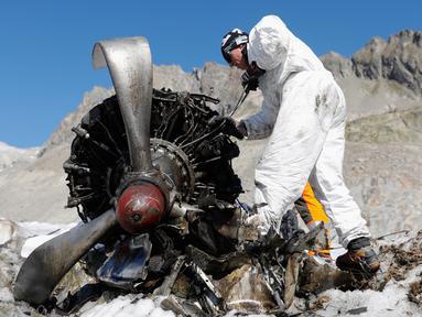 Anggota tentara Swiss mengecek mesin pesawat tempur Perang Dunia II milik AS saat ditemukan di Gauli Glacier, di Bernese Alps, Swiss (17/9). Pesawat Perang Dunia II C-53 Skytrooper Dakota tersebut jatuh tahun 1946. (Peter Klaunzer/Keystone via AP)