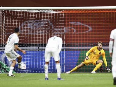 Penyerang Meksiko, Raul Jimenez (Kiri) melakukan tendangan penalti melawan penjaga gawang Belanda Tim Krul dalam pertandingan persahabatan antara Belanda dan Meksiko di Johan Cruyff Arena di Amsterdam (7/10/2020). Meksiko menang 1-0 atas Belanda. (AFP/ANP/Maurice Van Steen)