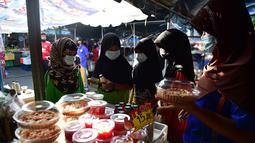 Sejumlah wanita mengenakan masker di pasar, sebagai bagian dari upaya untuk menghentikan penyebaran virus corona Covid-19, selama bulan suci Ramadhan di provinsi selatan Thailand, Narathiwat (17/4/2021). (AFP/Madaree Tohlala)