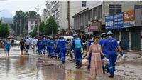Petugas melakukan pembersihan di Gongyi, dekat Zhengzhou, provinsi Henan, China (22/7). (AFP)