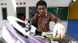 Hamidi saat memasukkan cairan bahan bakar buatannya kedalam kendaraan di bengkel kerjanya dekat TPA Rawa Kucing, Tangerang, (17/3). Hamidi membuat inovatif yang mengubah sampah plastik menjadi bahan bakar. (REUTERS / Beawiharta)