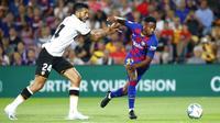 Penyerang Barcelona, Ansu Fati, berusaha melewati bek Valencia, Ezequiel Garay, pada laga La Liga di Stadion Camp Nou, Sabtu (14/9). Barcelona menang 5-2 atas Valencia. (AP/Joan Monfort)