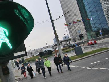 Orang-orang menyeberang jalan dengan lampu lalu lintas bergambar wanita di Vilnius, Lituania, Jumat (2/11). Hal itu untuk merayakan ulang tahun ke-100 wanita memperoleh pengakuan internasional dalam pemungutan suara di negara baltik. (Petras Malukas/AFP)