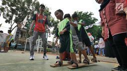 Anak-anak bermain permainan tradisional bakiak di RPTRA Melati Duri Pulo, Jakarta, Sabtu (13/10). Traditional Games Returns (TGR) mengampanyekan permainan tradisional Indonesia untuk membangkitkan eksistensinya. (Liputan6.com/Herman Zakharia)
