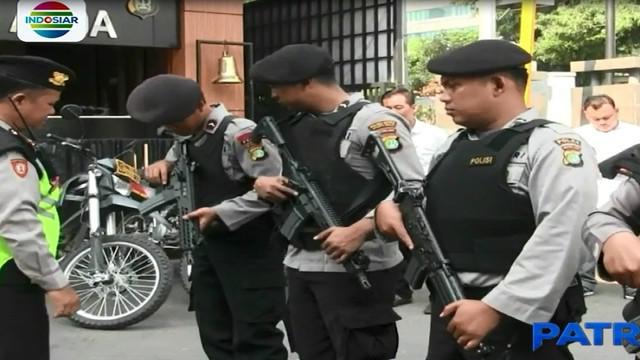 Pada Senin pagi, polisi menjaga Mapolsek Kebon Jeruk, dengan membawa senjata laras panjang.