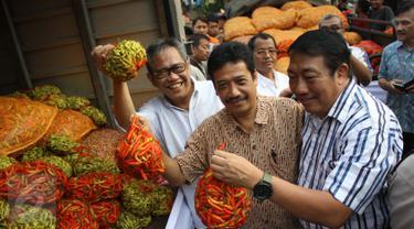 Dirut Bulog, Djarot Kusumayakti (kiri) mengangkat cabai saat operasi pasar di Pasar Induk Kramat Jati, Jakarta, Sabtu (15/8/2015). Operasi pasar ini untuk menekan kenaikan harga cabai yang mencapai Rp 70.000/kg. (Liputan6.com/Gempur M Surya)