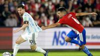 Pemain Argentina, Lionel Messi (kiri) berusaha melepaskan diri dari adangan pemain Paraguay, Junior Alonso (kanan) dalam lanjutan Kualifikasi Piala Dunia Zona CONMEBOL, Jumat (8/10/2021) dini hari WIB. (AP Photo/ Jorge Saenz)