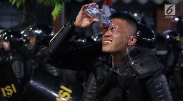 Personil Kepolisian dari satuan Brimob membasuh wajah di sela-sela tugas menghalaumassa yang berlakuanarkis di sekitardepanGedungBawaslu, Jalan MH Thamrin, Jakarta, Rabu (22/5/2019). Aksiunjuk rasa yang dimotori GNKR berakhirricuh. (Liputan6.com/HelmiFithriansyah)